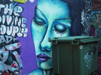 Woman's face mural with bin